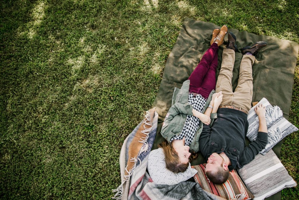 couple talking and lying in the grass